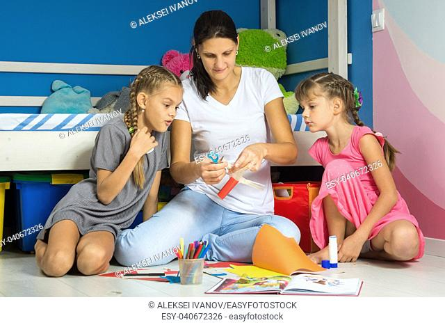 Mom shows daughters how to cut out figures from colored paper