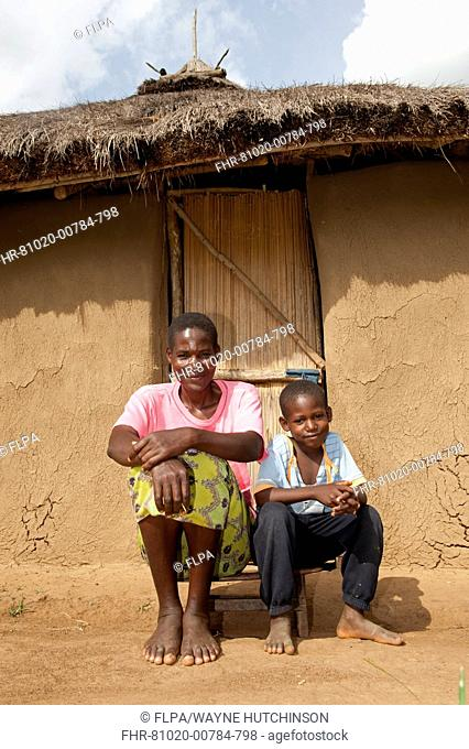 Mother and son sitting on low stool outside traditional home made from mud with thatched roof, Kenya, June