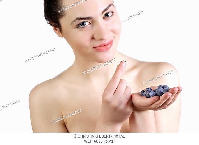 Beautiful woman eating fresh blueberries