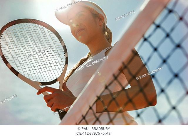 Confident young female tennis player holding tennis racket at net