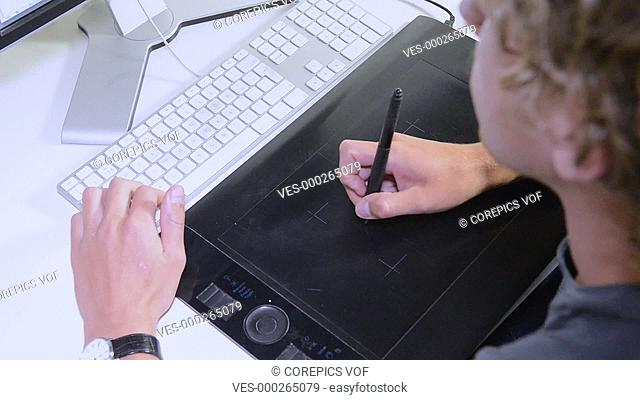 Product engineer at work creating conceptual sketches using a tablet and a computer