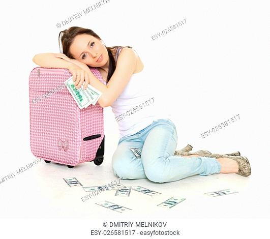 Young woman with suitcase and money sits on a white background. Vacation