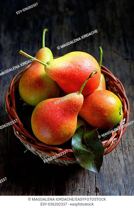Pears in a basket on wooden table