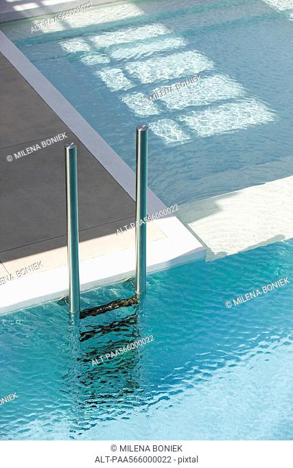 Swimming pool ladder at deep end separated from shallow pool by ledge