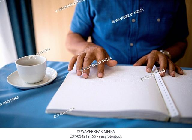 Midsection of senior man reading book by coffee cup at table