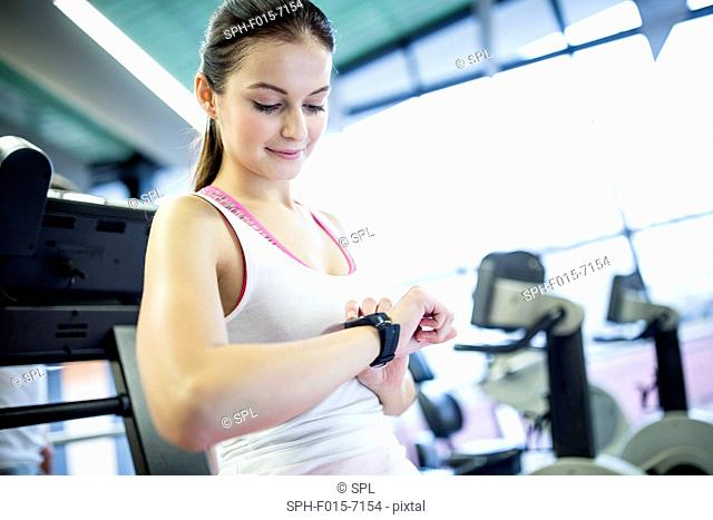 MODEL RELEASED. Woman using smart watch in gym