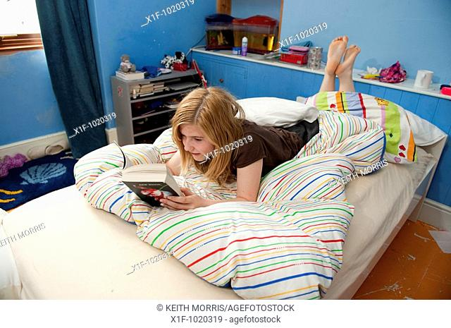 14 year old Teenage girl reading a book lying on the bed in her bedroom