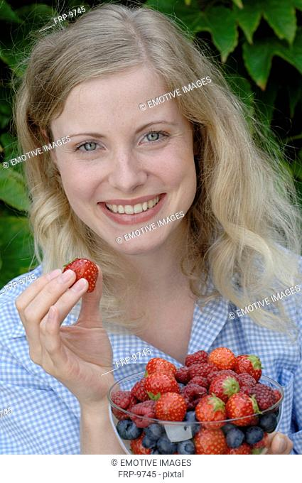 Woman holding bowl with fruit