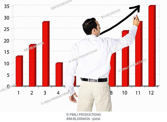 Hispanic businessman drawing bar graph on board