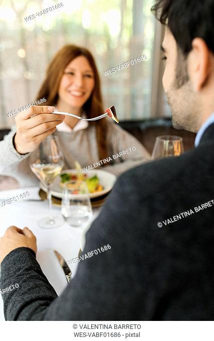 Smiling woman letting man taste the food in a restaurant