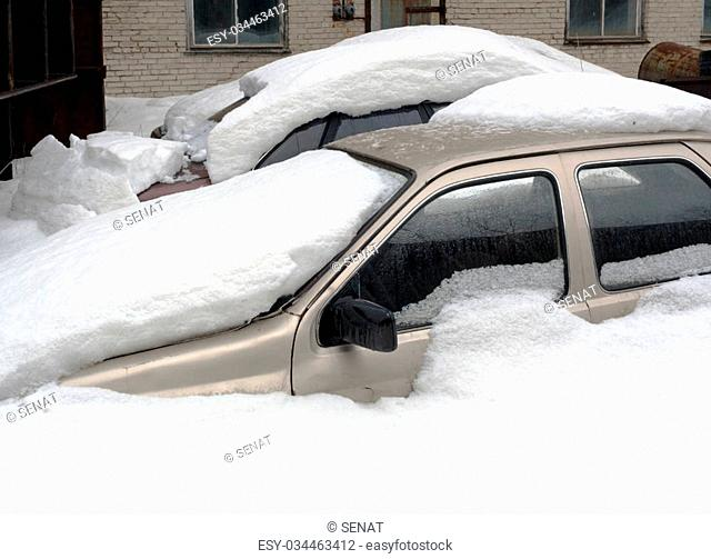 Two car completely buried in snow on a background of a brick wall with windows in winter
