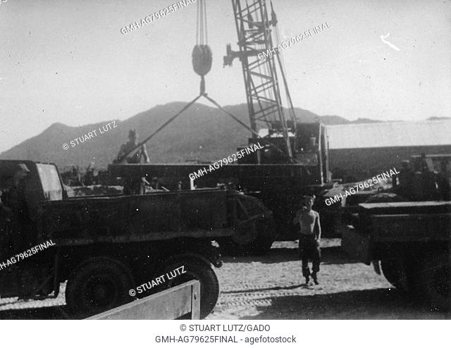 A photograph of United States Army servicemen unloading a steel i-beam from a truck using a crane, Vietnam, 1967