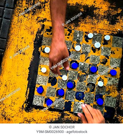 Hands of Salvadoran men are seen moving plastic bottle caps while playing checkers on an outdoor checkerboard table in the park in San Salvador, El Salvador
