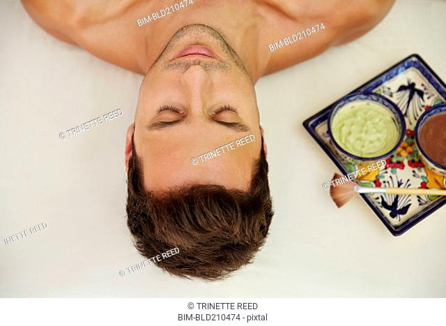 Mixed race man laying on massage table