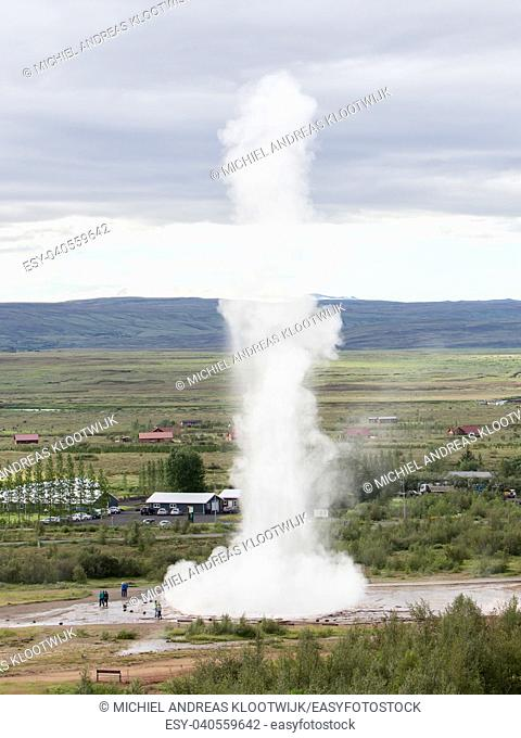 Impressive eruption of the biggest active geysir, Strokkur, with tourists waiting around, Golden circle, Iceland