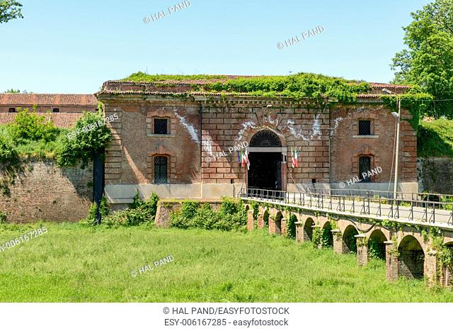 monumental entrance of Cittadella fortifications, Alessandria, Italy, view of entrance door in the brick walls on the green dry moat of ancient fortified part...