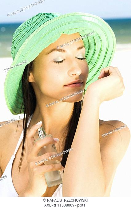 woman applying perfume on beach