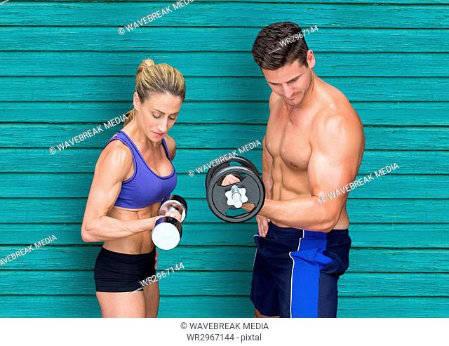 fitness couple with wights with light blue wood background