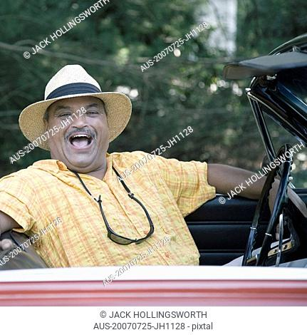 Portrait of a senior man sitting in a convertible car and laughing