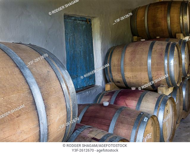 Wine Estate. Barrels of maturing wines, stacked and left in the quiet darkness of the wine cellar on a wine farm. Western Cape Province, South Africa