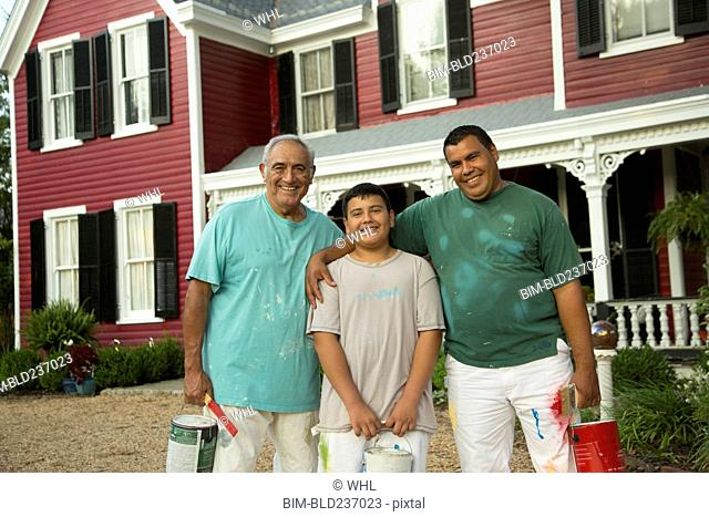 Smiling Hispanic men and boy posing with paint cans