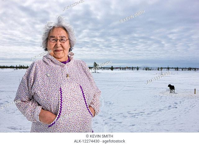 Elder Alaska native woman wearing a Kuspuk parka stands on snow covered tundra, Winter, Noatak, Arctic Alaska, USA