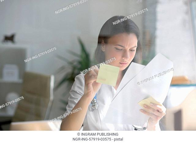 Medical doctor writing patient test results on transparent board to diagnose