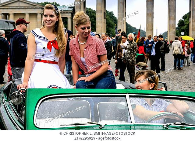 Models dressed in 1950s clothes pose for photographers at a car show in Berlin Gemrany