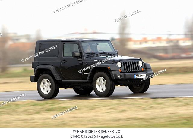 Jeep Wrangler Rubicon 3.8, model year 2008-, black, driving, diagonal from the front, frontal view, side view, country road