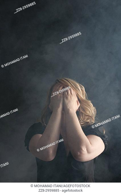 Woman hiding face with hands in fear