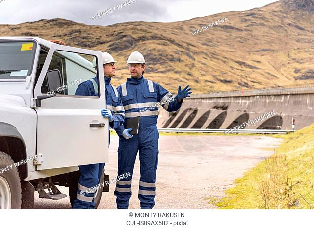 Workers with utility vehicle by dam at hydroelectric power station