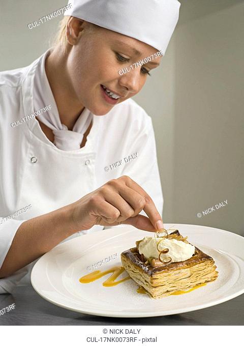 A female chef finishing a desert