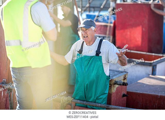 Fisherman on trawler talking to inspector