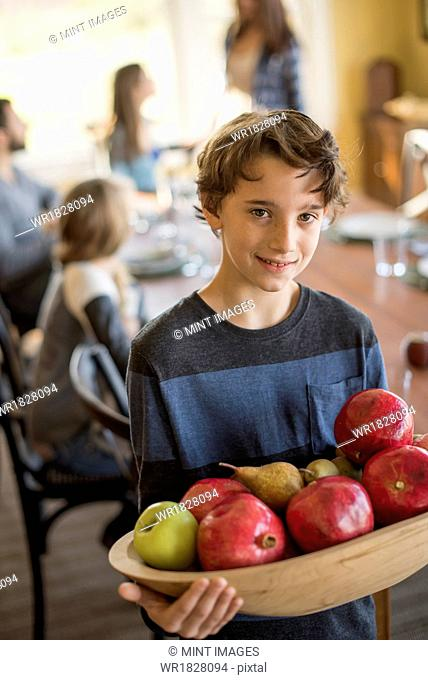 A boy carring a wooden tray of apples