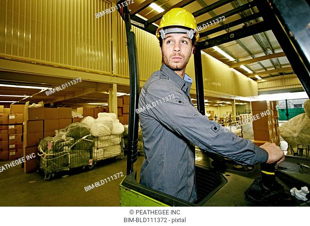 Caucasian worker driving machinery in warehouse
