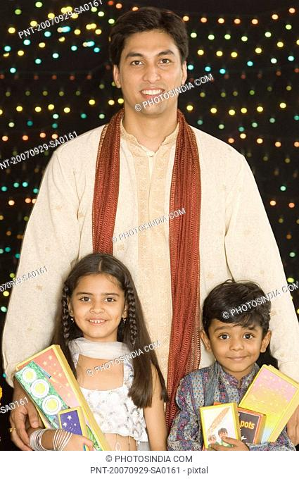 Portrait of a young man standing with his son and daughter and holding diwali crackers