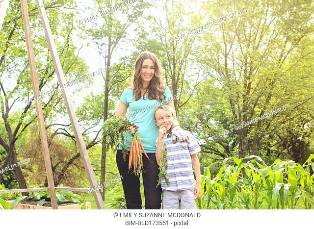 Caucasian mother and son holding carrots in garden
