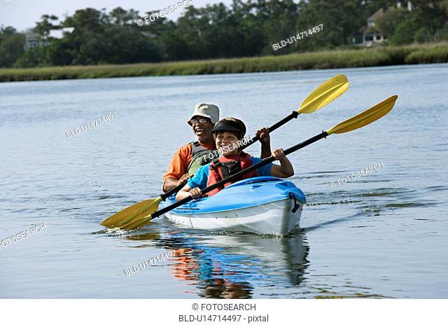 Couple smiling and paddling kayak
