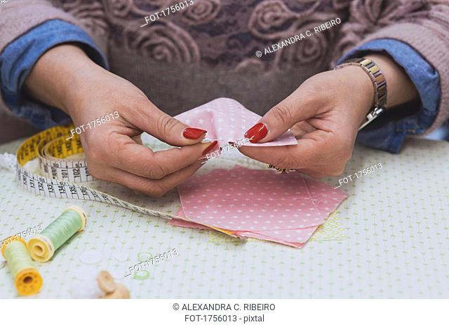 Midsection of fashion designer sewing pink fabrics