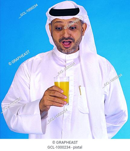 Arab man holding a glass with orange juice