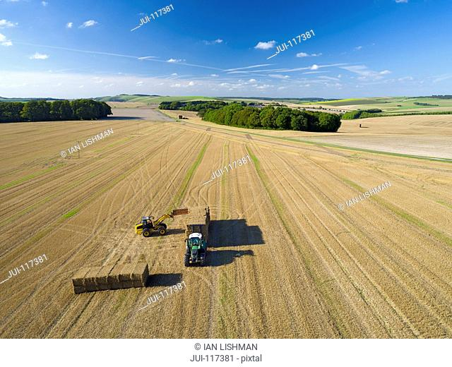 Aerial View Of Loading Bales Onto Trailer After Harvest