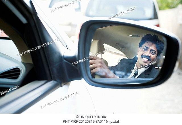 Reflection of a South Indian businessman in the side view mirror of a car