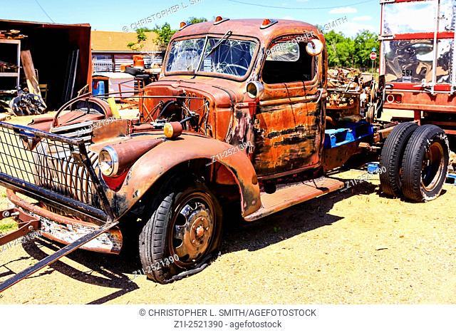 An un restored 1940s Ford flatbed truck in a collectors yard in Tucumcari New Mexico