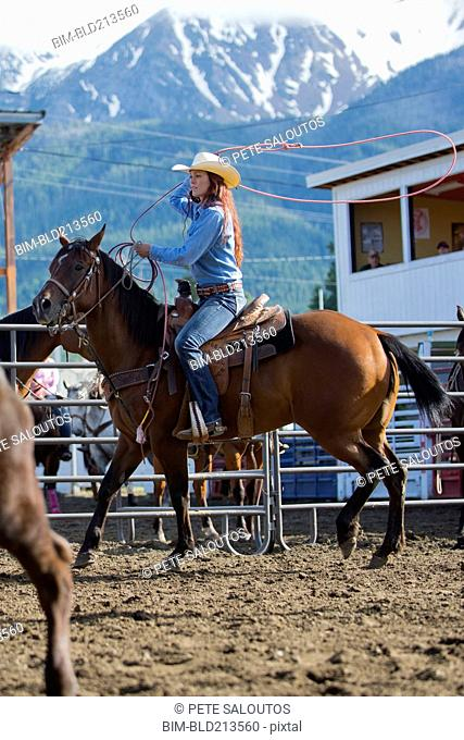 Caucasian cowgirl riding horse in rodeo on ranch