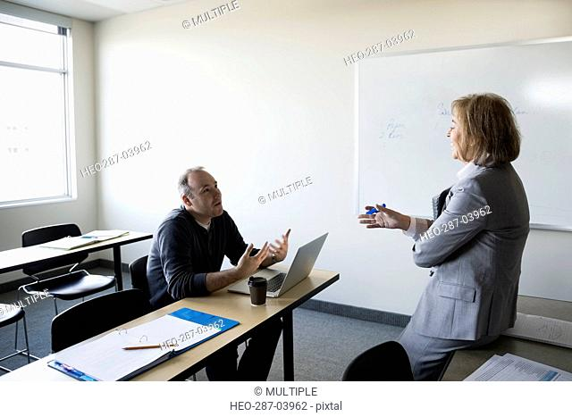 Professor and adult education student talking in classroom