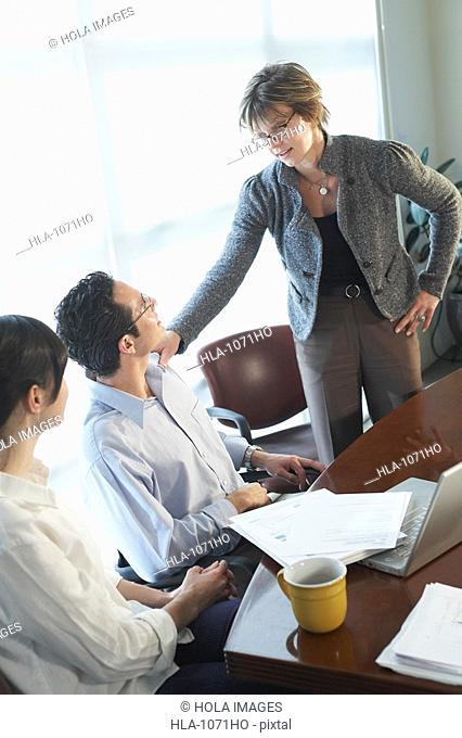 Businesswoman keeping her hand on a businessman's shoulder