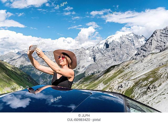 Woman taking selfie in front of mountains, Passo di Stelvio, Stelvio, Italy