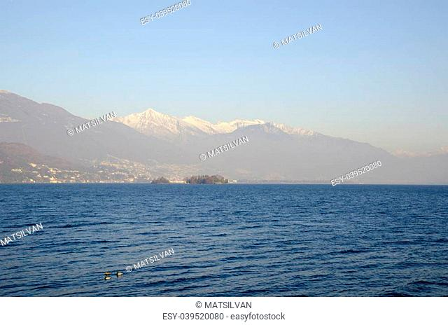 Misty alpine lake with islands and snow-capped mountain and blue sky