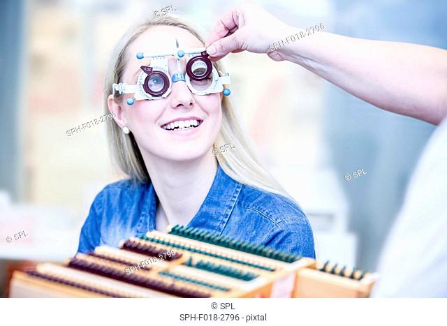 Cheerful young woman having eye examination in optometrist's shop, close-up