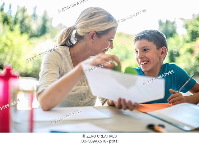 Mother and son sitting together, mother helping son with homework